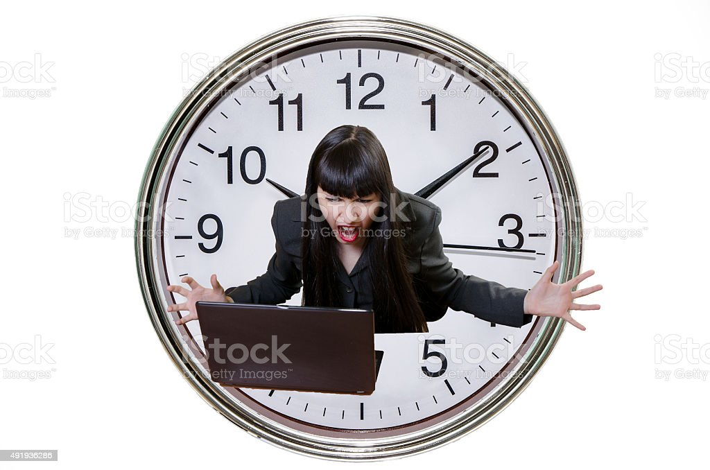 Business woman yelling at her laptop with big clock background stock photo