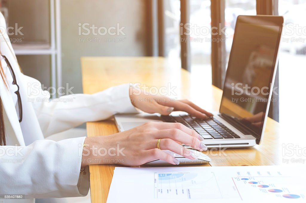 Business woman's hands typing on laptop keyboard stock photo
