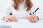 Business women filling contract at desk.