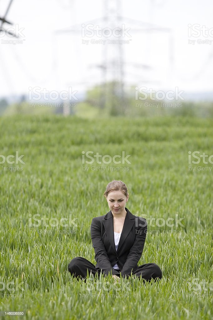 Business women sits in green field royalty-free stock photo