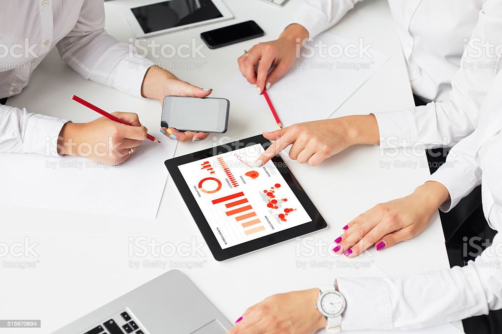 Business women using tablet computer in meeting stock photo