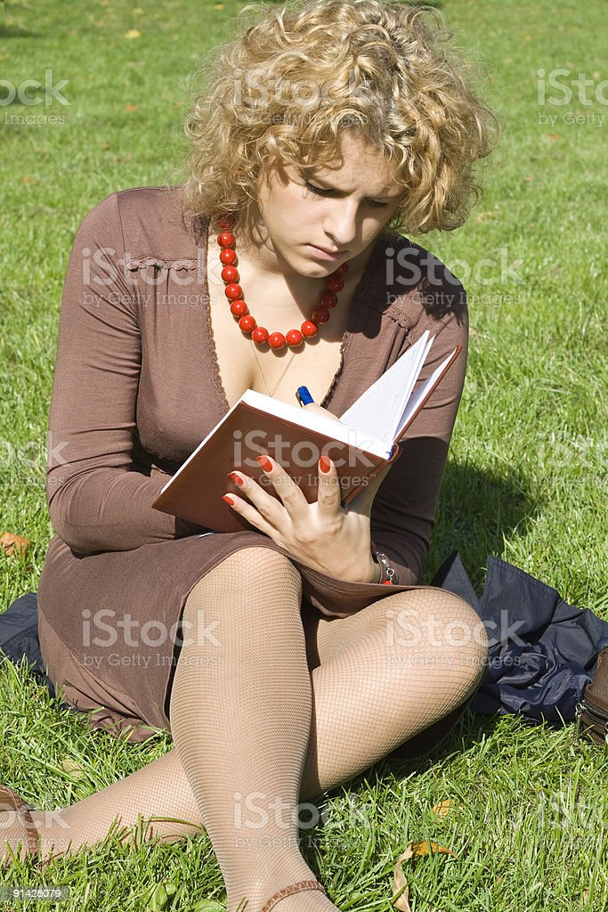 Business women with notebook sits on grass stock photo