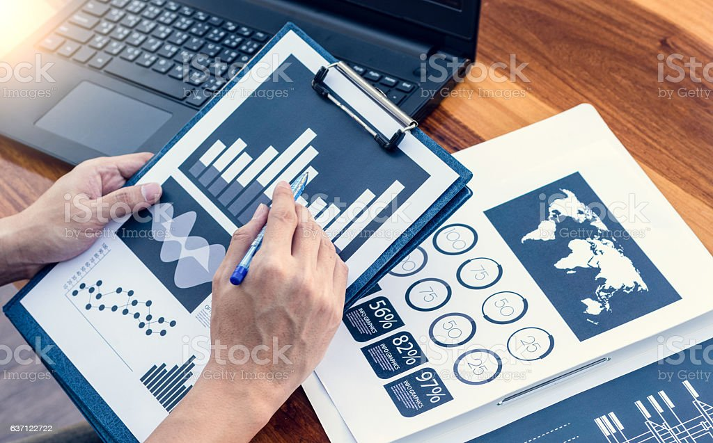 Business workers discussing digital graphs and diagrams indicati stock photo