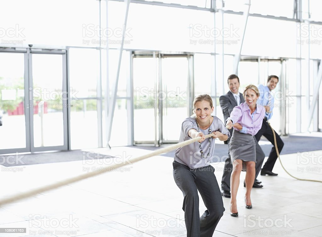 Business workers in a tug-of-war pulling a rope stock photo