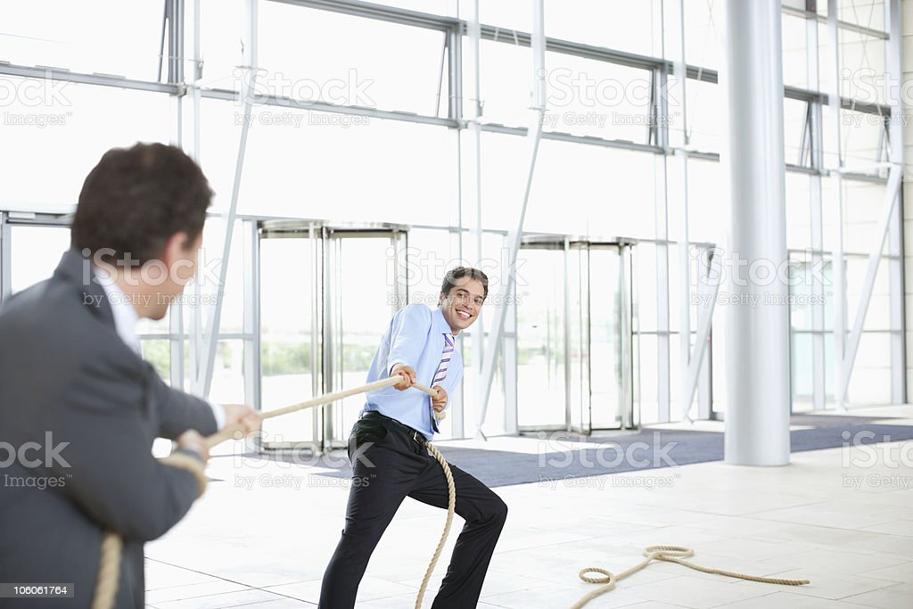 Business workers in a tug-of-war pulling a rope royalty-free stock photo