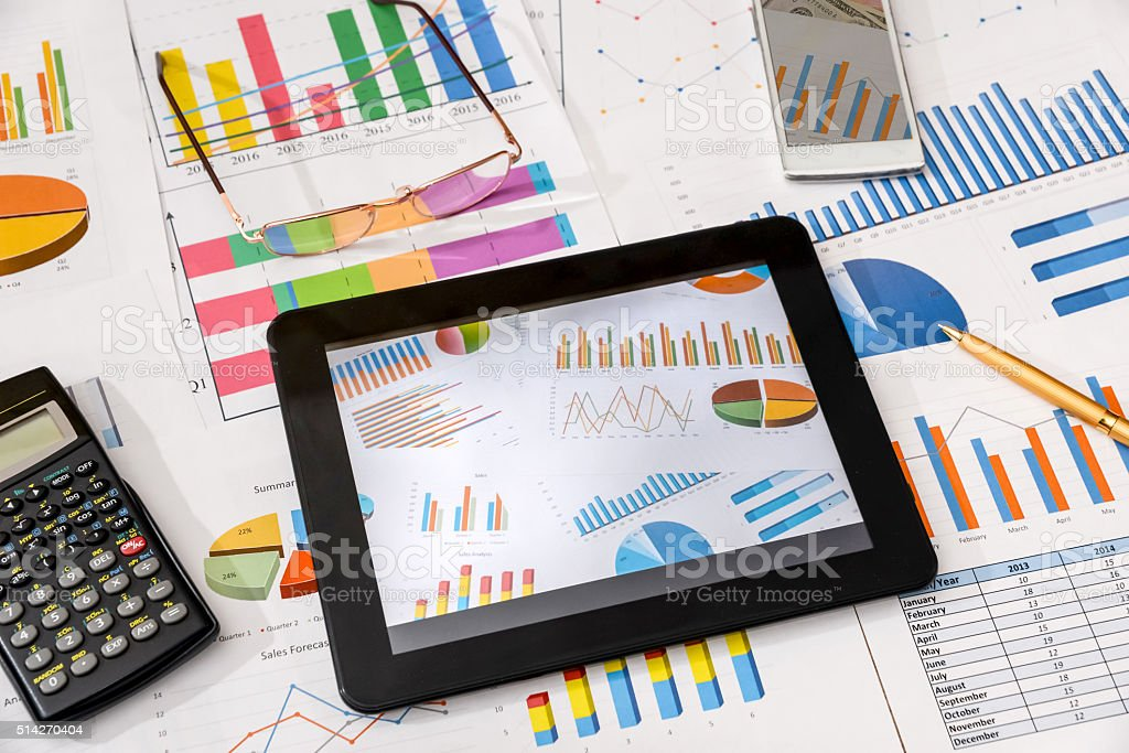 business workplace with tablet, smartphone and charts and graphs, pen stock photo