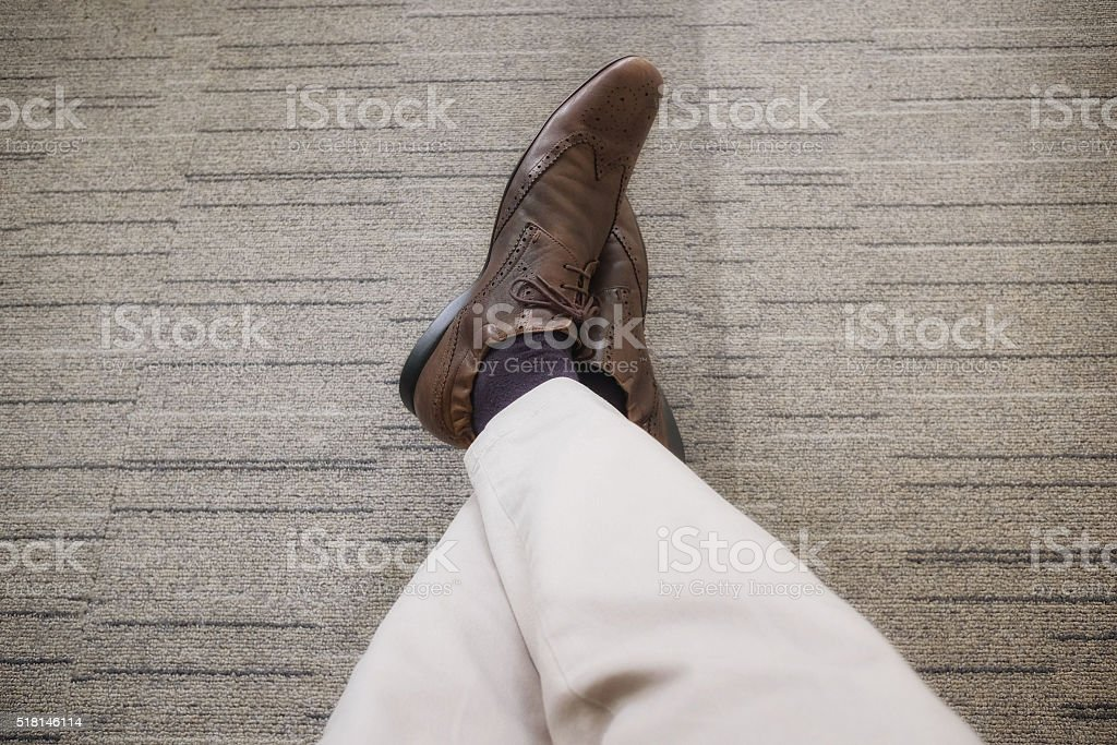 business young man relaxing legs crossed on carpet floor stock photo