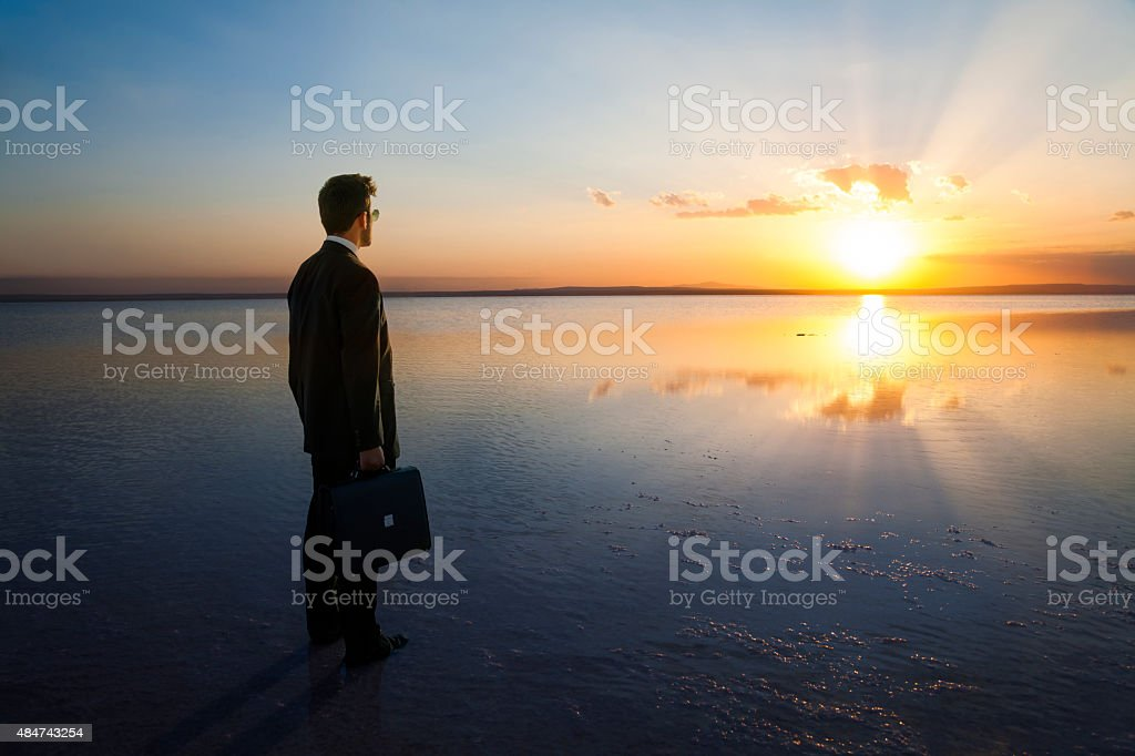 Businessm watching the sunset stock photo