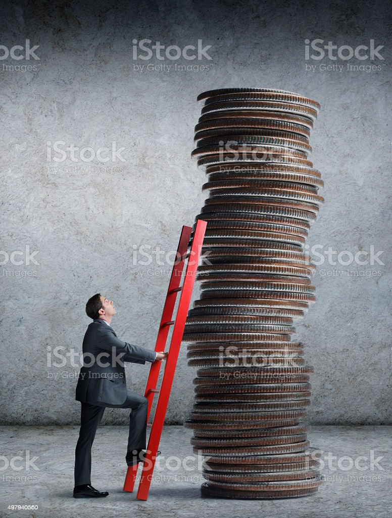 Businessman About To Climb Ladder Leaning Against Stack Of Coins stock photo