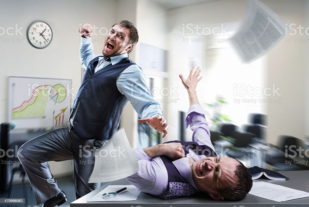 Businessman about to punch a coworker in the office  stock photo