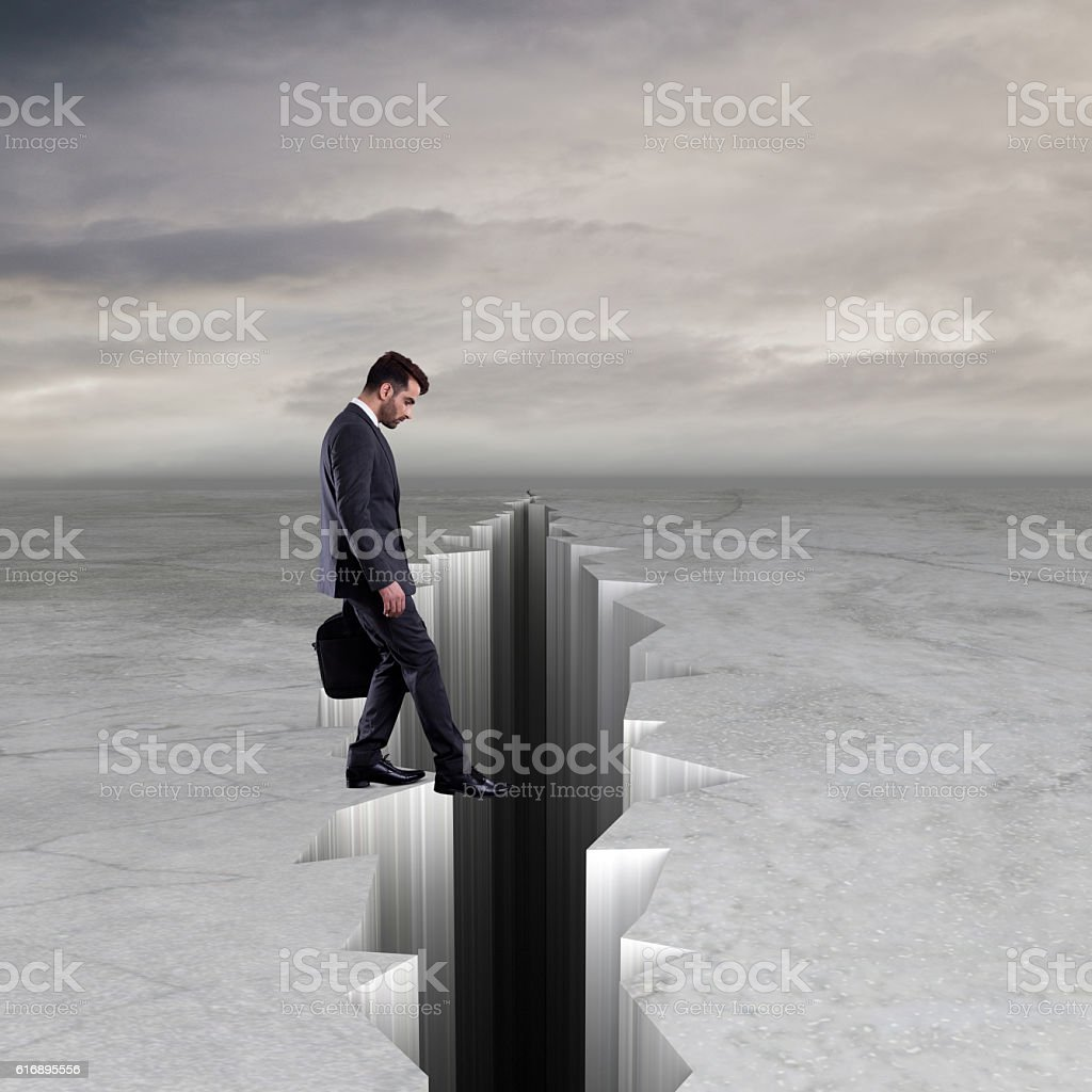Businessman about to step into crack stock photo
