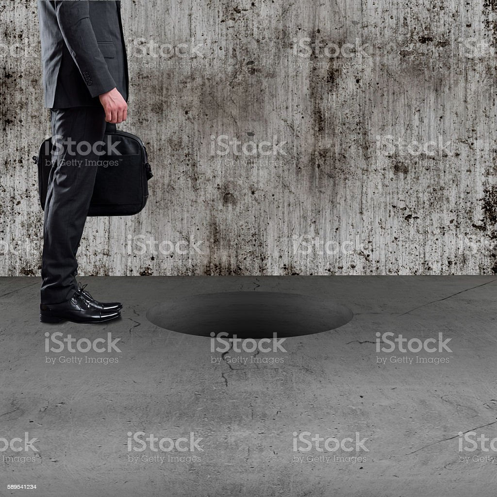 Businessman about to step into large hole stock photo