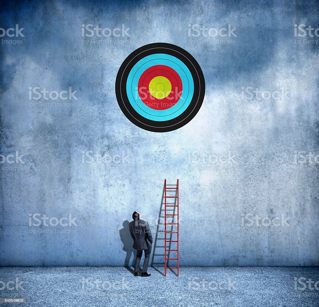 Businessman About To Use Ladder To Reach Target stock photo