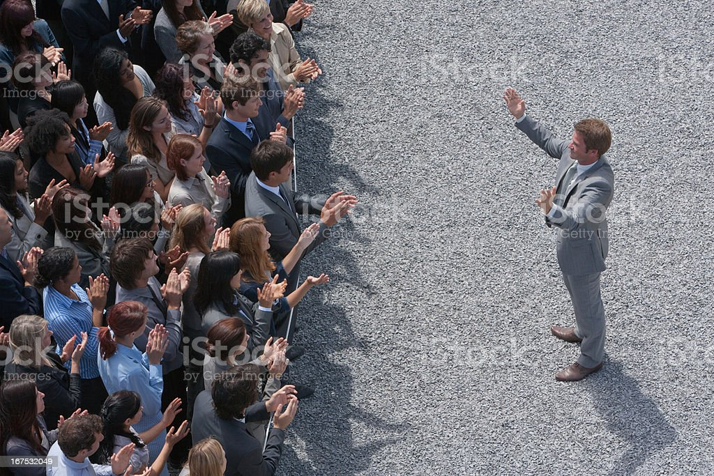 Businessman addressing clapping crowd stock photo