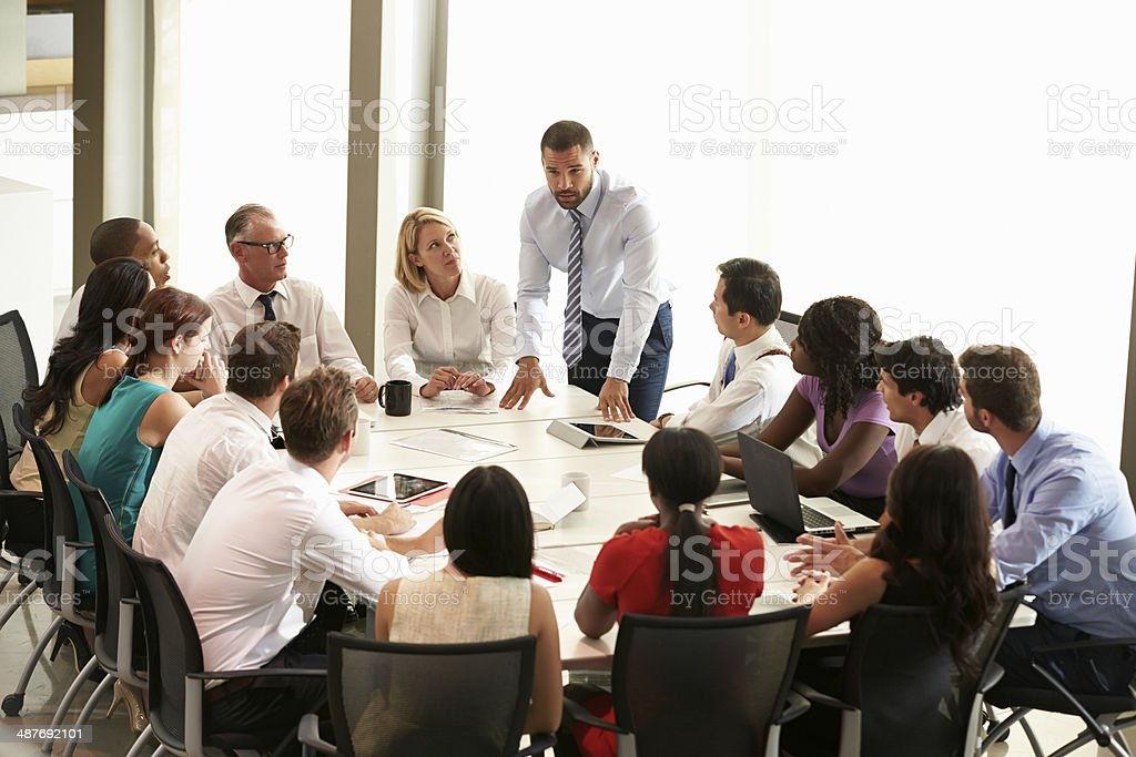 Businessman addressing collegues around table stock photo