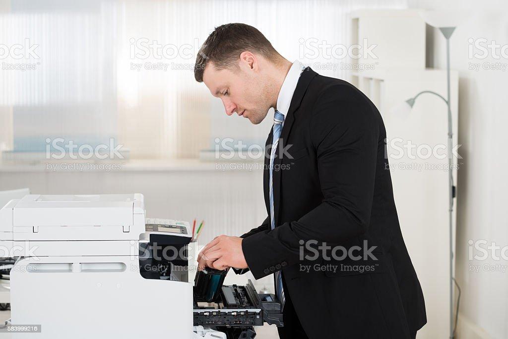 Businessman Adjusting Cartridge In Photocopy Machine stock photo