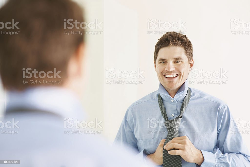 Businessman adjusting necktie in front of mirror royalty-free stock photo