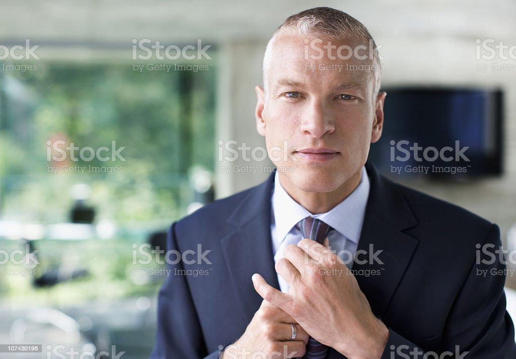 Businessman adjusting necktie stock photo