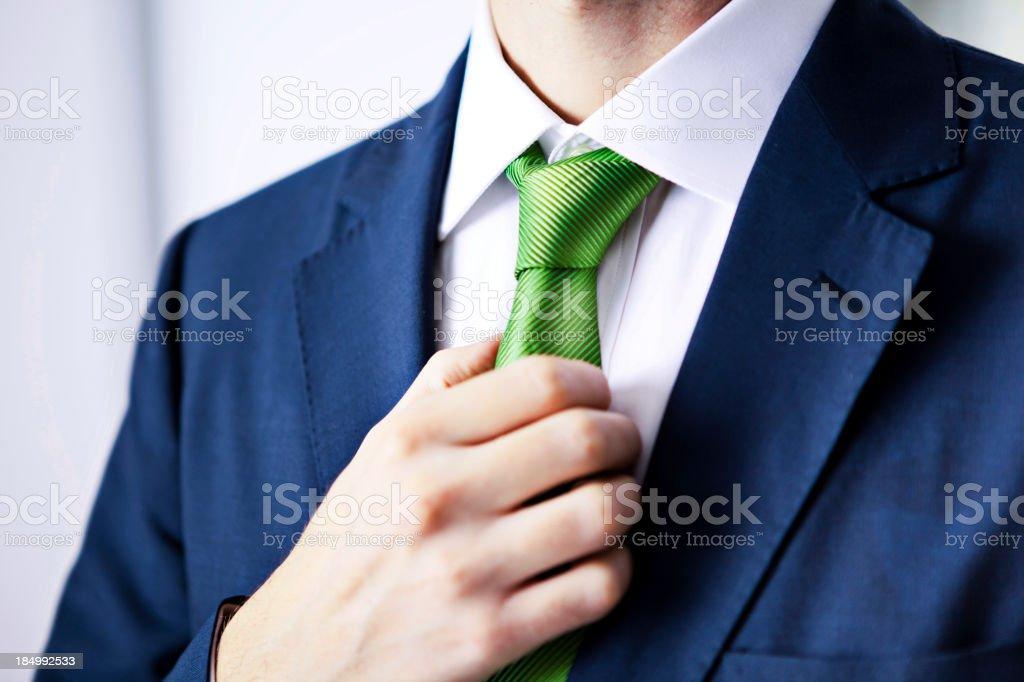 Businessman adjusting tie stock photo