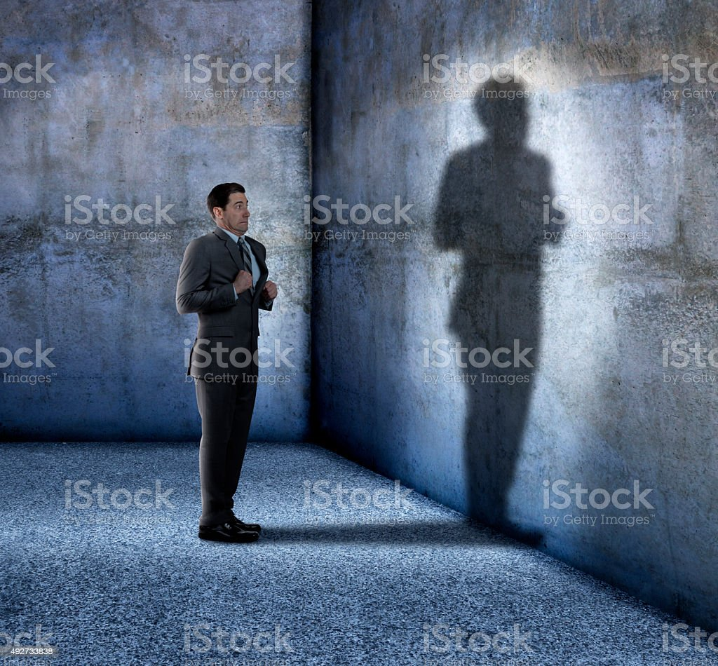Businessman Afraid Of His Own Shadow stock photo