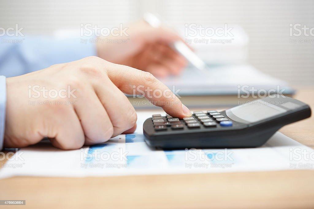 Businessman analyzing business data and using calculator stock photo