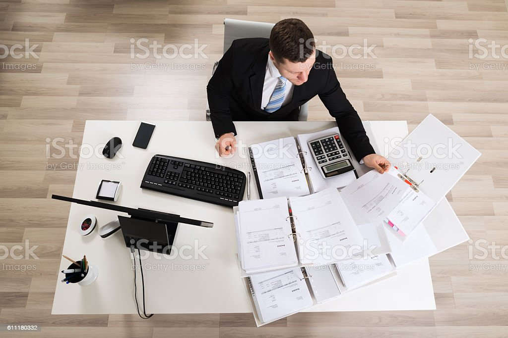 Businessman Analyzing Documents At Computer Desk stock photo