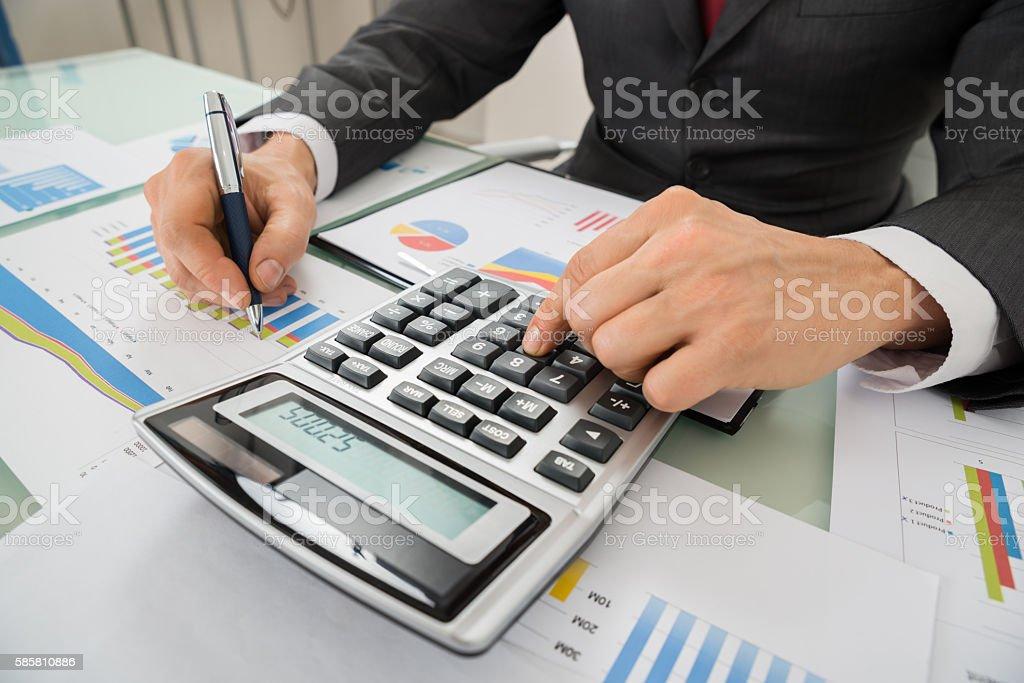 Businessman Analyzing Graph And Using Calculator - foto de stock