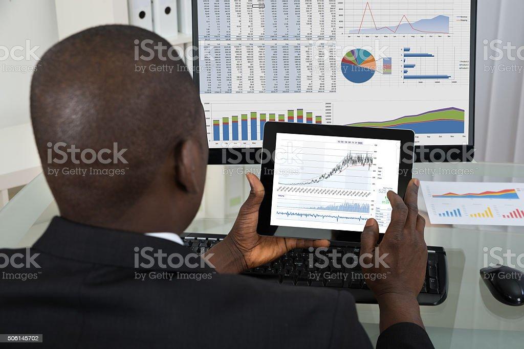 Businessman Analyzing Graph On Digital Tablet stock photo