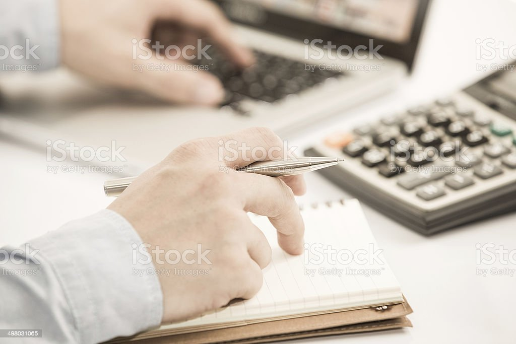Businessman analyzing investment charts with laptop stock photo
