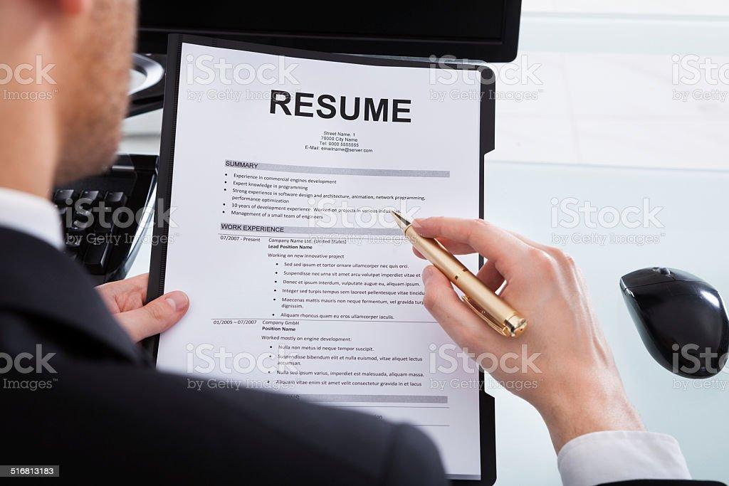 Businessman Analyzing Resume At Office Desk stock photo
