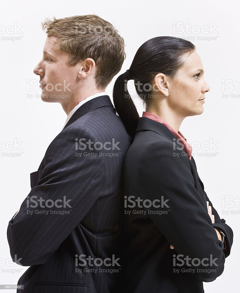 A businessman and a woman with their backs touching stock photo