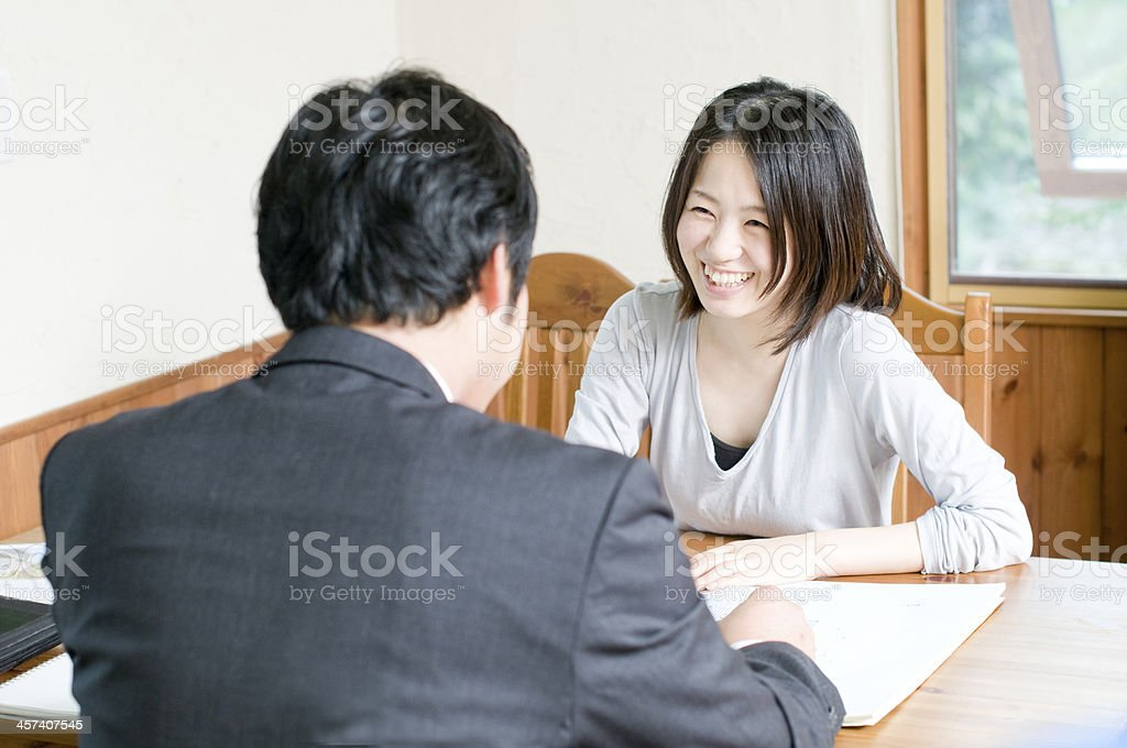 Businessman and and woman negotiating at a table stock photo