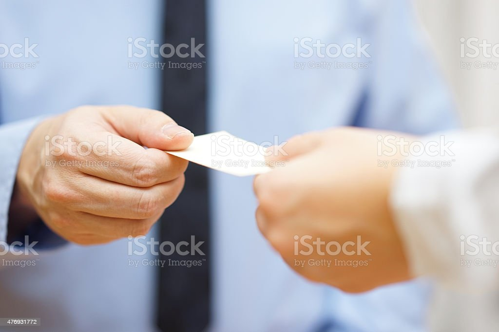 businessman and businesswoman are exchanging business cards stock photo
