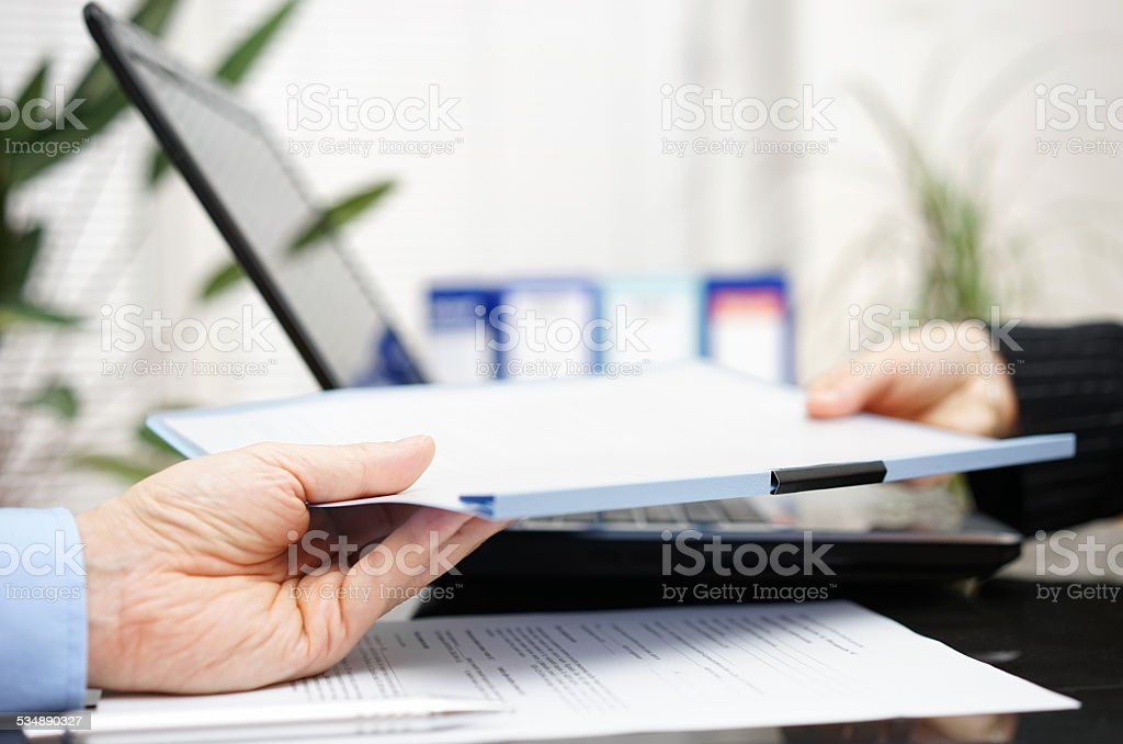 businessman and businesswoman are exchanging document or contract stock photo