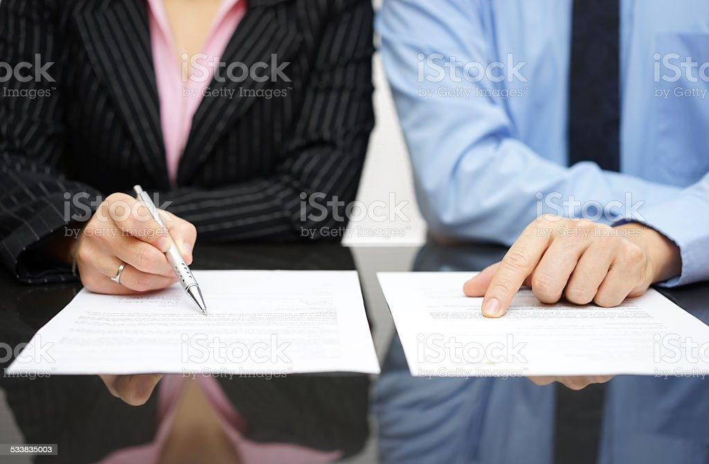 businessman and businesswoman are inspecting  contract stock photo
