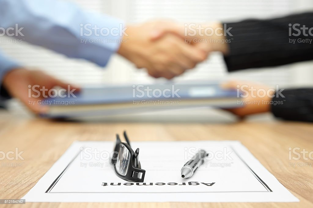 businessman and businesswoman are shaking hands and exchanging folder stock photo