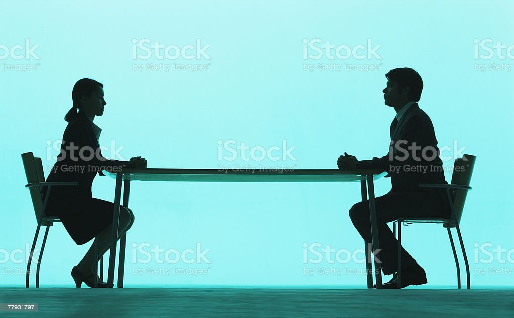 Businessman and businesswoman at a table stock photo