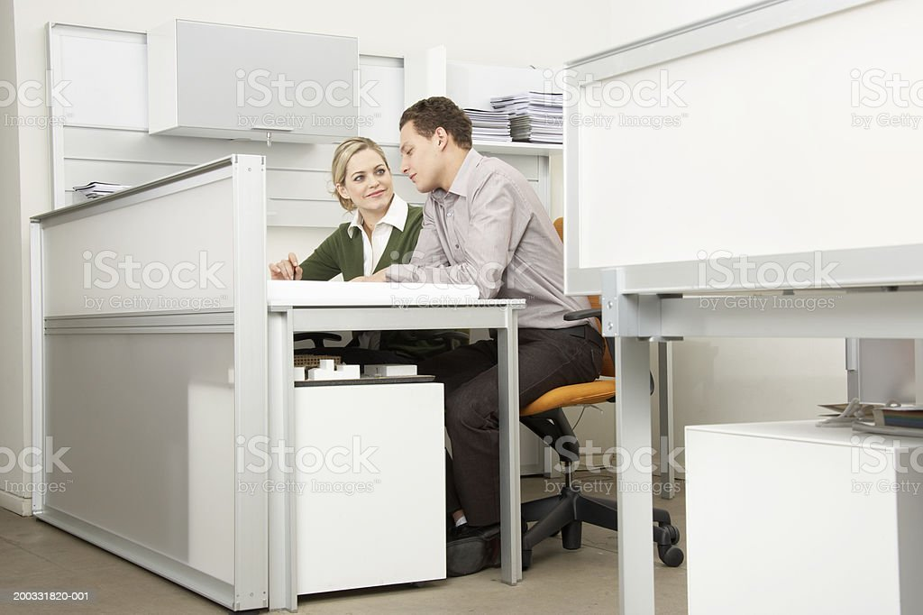 Businessman and businesswoman at desk in office royalty-free stock photo