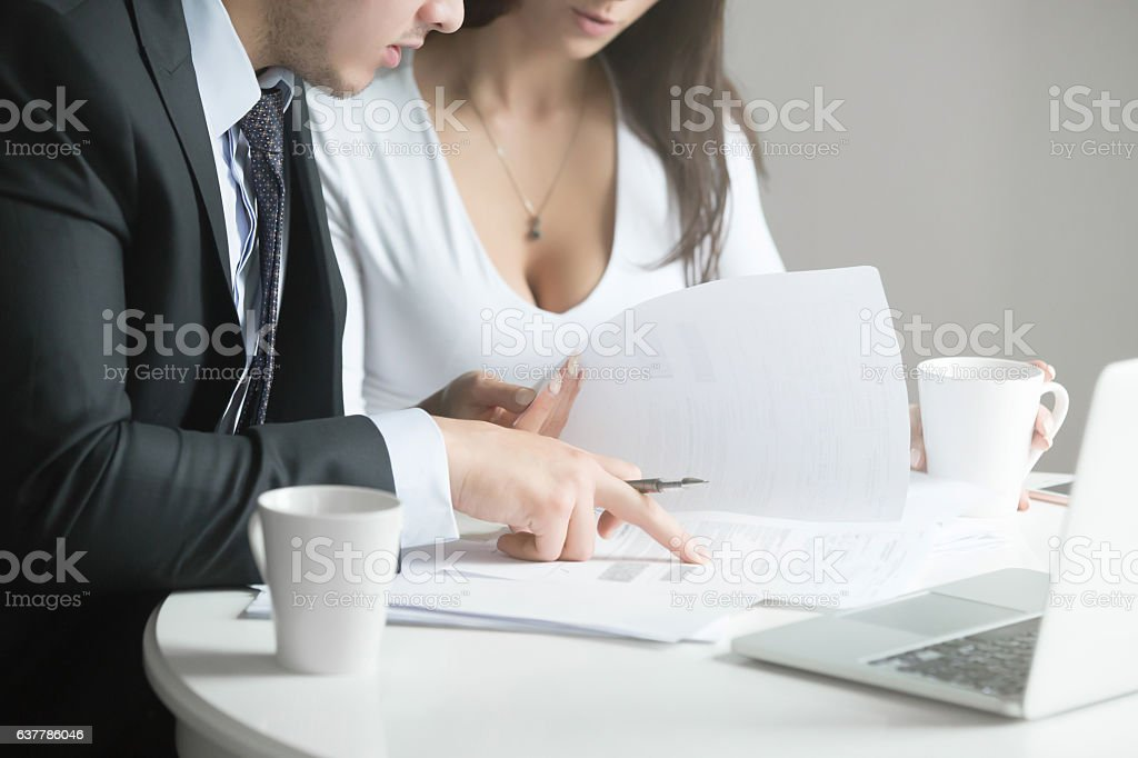 Businessman and businesswoman at office desk, working together w stock photo