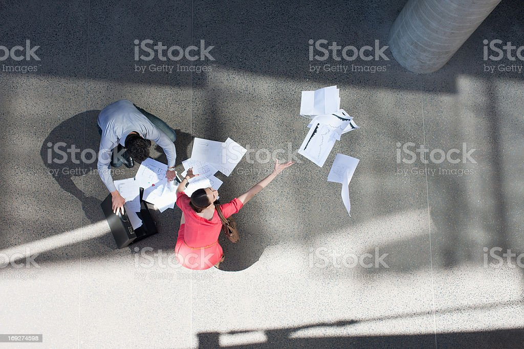 Businessman and businesswoman collect  paper  royalty-free stock photo