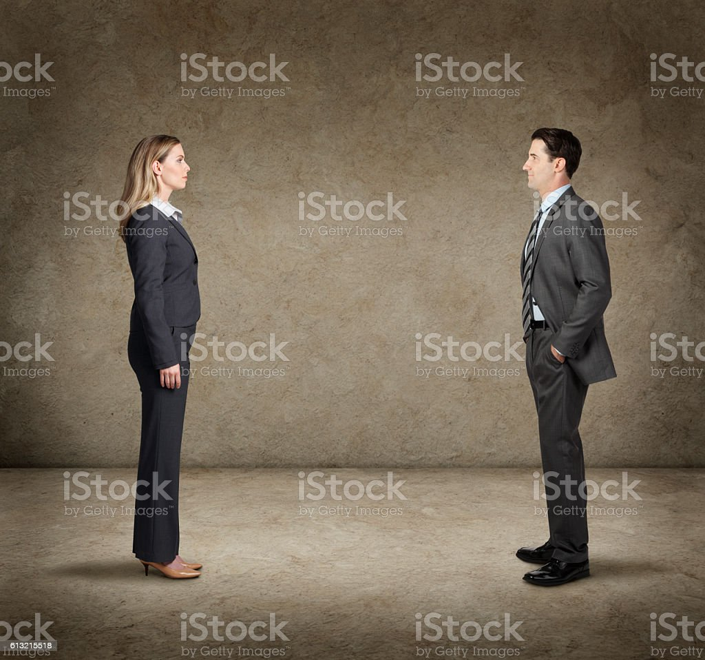 Businessman And Businesswoman Confront Each Other In Faceoff stock photo