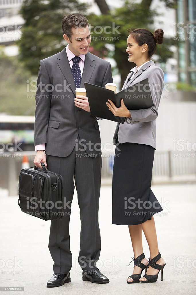 Businessman And Businesswoman Discussing Document In Street royalty-free stock photo