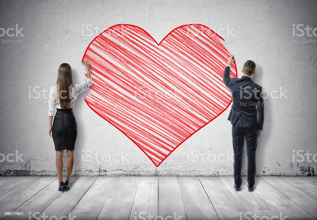 Businessman and businesswoman drawing big red heart on concrete wall stock photo