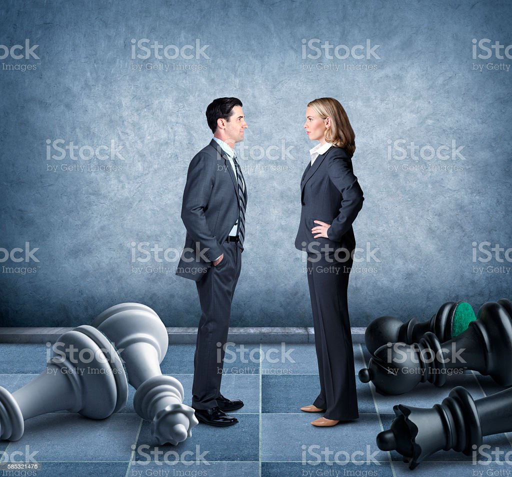 Businessman And Businesswoman Facing Off On Chessboard stock photo