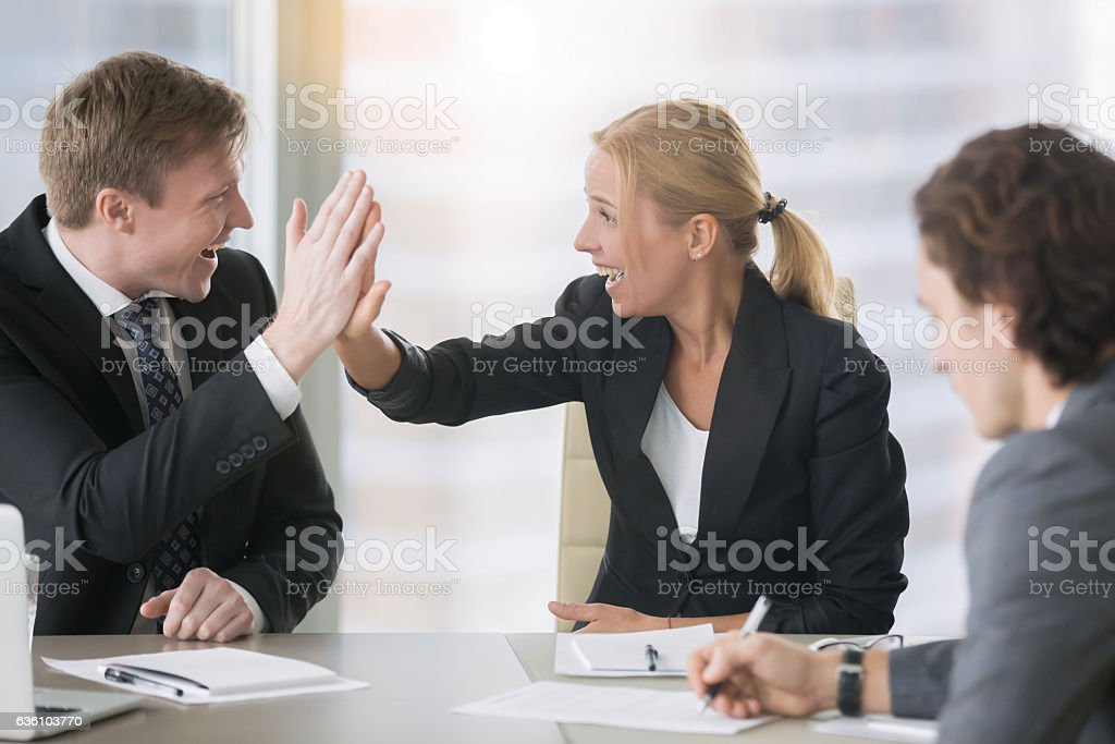 Businessman and businesswoman giving a high five stock photo