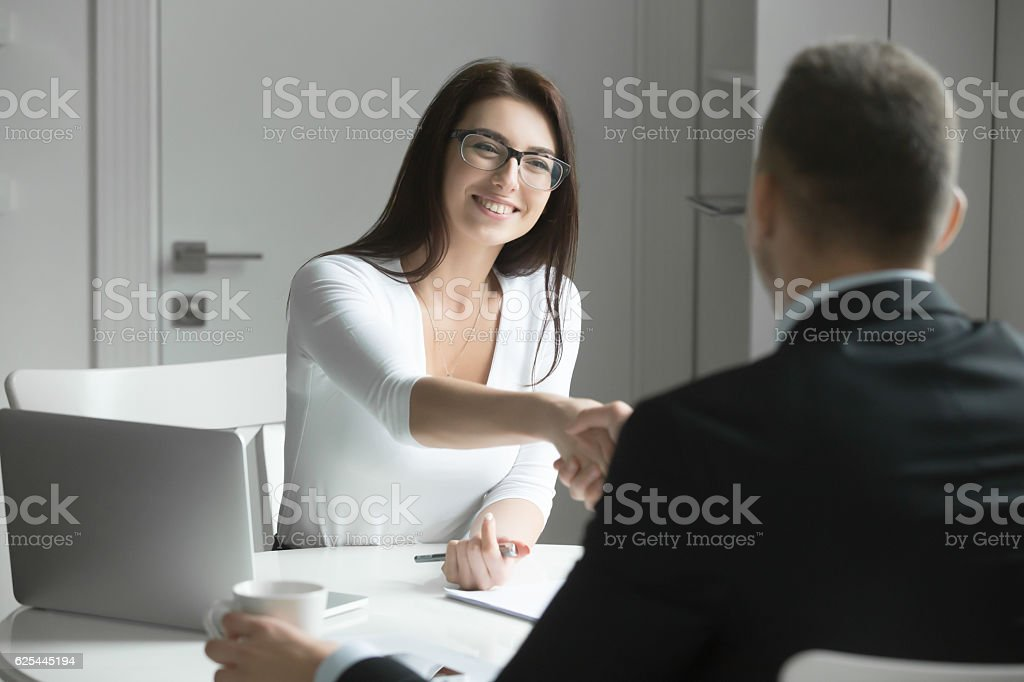 Businessman and businesswoman handshaking over the office desk stock photo