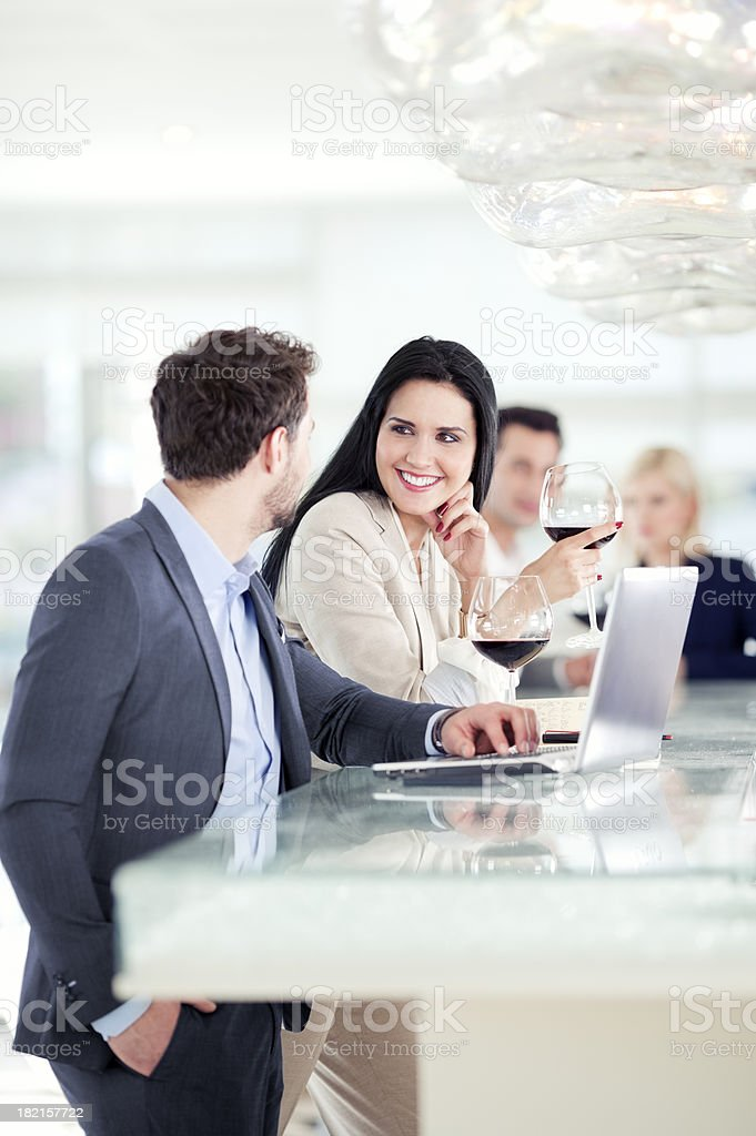 Businessman and businesswoman having drink in bar, looking at laptop royalty-free stock photo