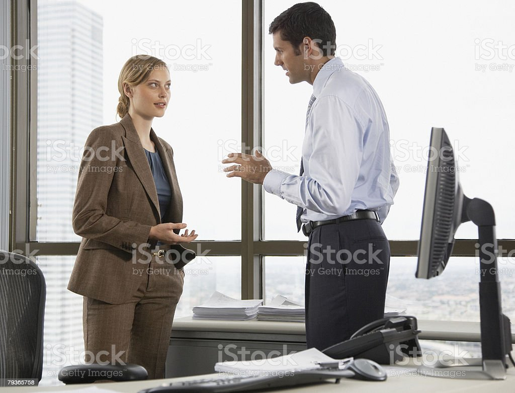 Businessman and businesswoman in an office talking royalty-free stock photo