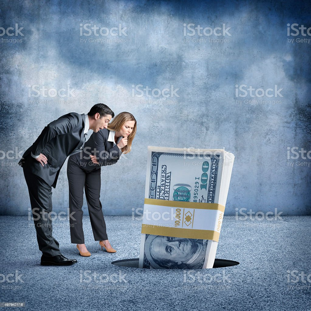 Businessman And Businesswoman Look At Money Going Down A Hole stock photo