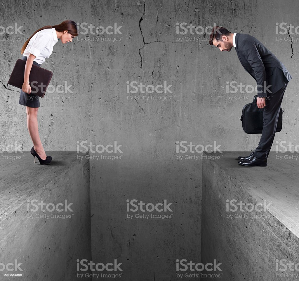 Businessman and businesswoman looking down into divide stock photo